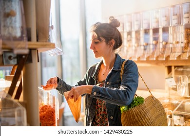 Beautiful young woman shopping in a bulk food store. She buys organic pasta