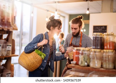 Beautiful young woman shopping in a bulk food store. The seller advises her to buy organic spices in jars.
