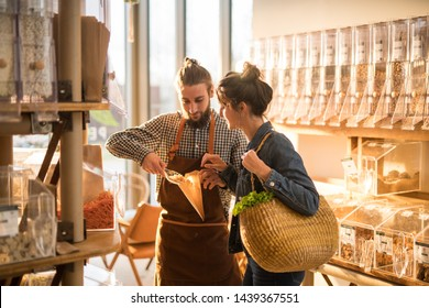 Beautiful young woman shopping in a bulk food store. The seller advises her on her purchases of organic food