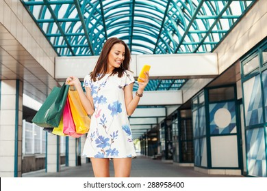 Beautiful young woman in shopping using a mobile phone