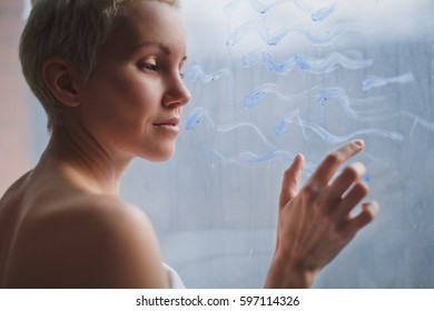 Beautiful young woman with short blond hair standing at the window and draws a blue sea waves