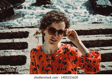 Beautiful young woman with short curly hair looking at camera. Female retro sun protection sunglasses. Enjoy summer vacation concept. Close up portrait girl. Black Sea background. Travel to Ukraine
