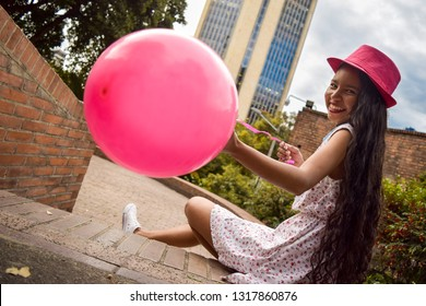 Beautiful young woman with short dress and hat, smiles while holding a globe in her hands, she is sitting on the stairs