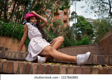 Beautiful young woman with short dress, hat and pretty legs is sitting on some stairs