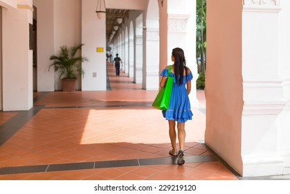 beautiful young woman in a short dress shopping in the city, holding shopping bag