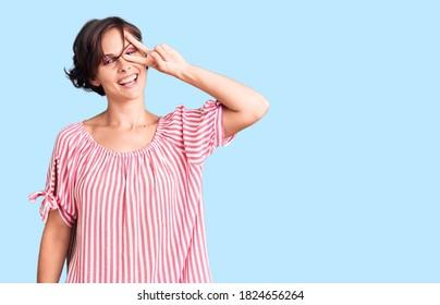 Hermosa joven con el pelo corto vestido casual de verano haciendo símbolo de paz con los dedos sobre la cara, sonriendo alegre victoria