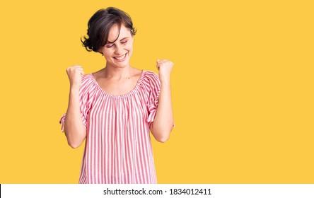 Hermosa joven con el pelo corto usando ropas casuales de verano emocionada por el éxito con los brazos levantados y los ojos cerrados celebrando la victoria sonriendo. concepto de ganador.