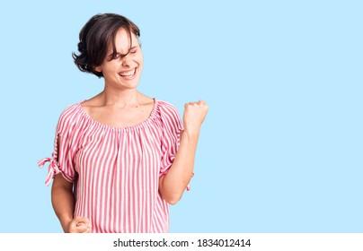 Hermosa joven con el pelo corto vestido casual de verano celebrando sorprendida y asombrada por el éxito con los brazos levantados y los ojos cerrados. concepto de ganador.