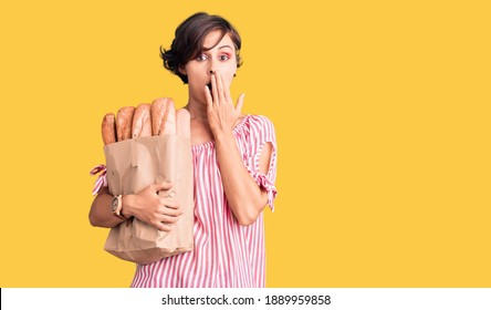Beautiful young woman with short hair holding paper bag with bread covering mouth with hand, shocked and afraid for mistake. surprised expression