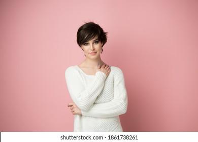 Schöne junge Frau mit Aufnahme dunkler Haare einzeln auf rosafarbenem Hintergrund.