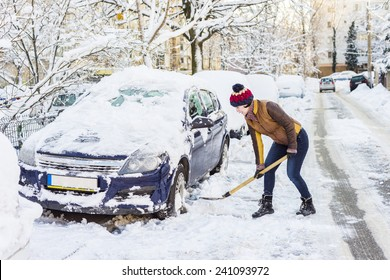 Beautiful young woman shoveling her car after a Snowstorm