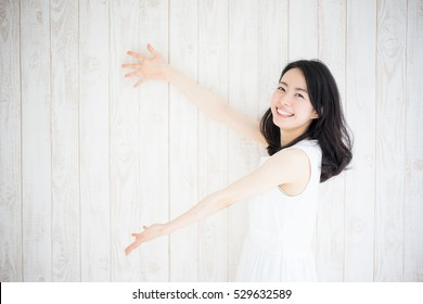 beautiful young woman showing copy space against white wooden wall