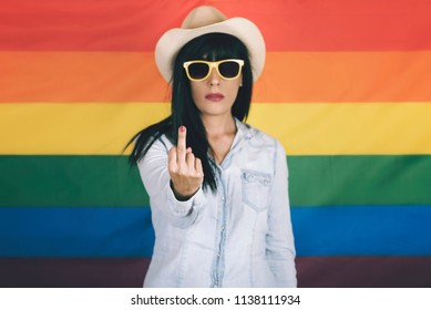 Beautiful young woman showing middle finger on rainbow flag background