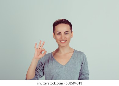 Beautiful young woman showing Ok sign isolated on green white wall background. Positive human emotions face expression body language. Horizontal studio shot