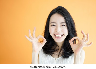 Beautiful young woman showing OK gesture against orange background.