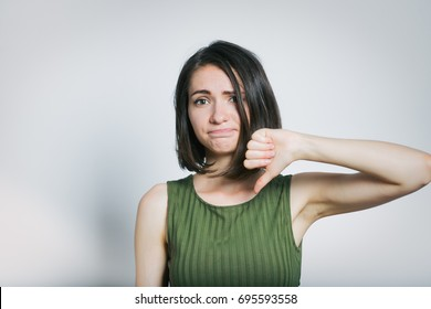 beautiful young woman showing thumbs down sign to dislike, isolated on background