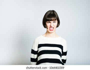 beautiful young woman shows it disgustingly, short haircut, studio photo on background
