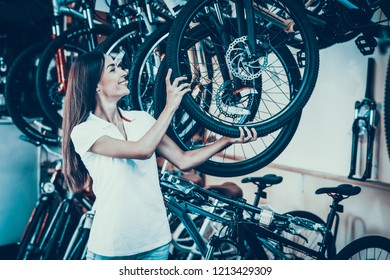 Beautiful Young Woman Shows Row of Modern Bicycles. Portrait of Cheerful Stylish Caucasian Female Seller Wearing White T-Shirt Holds Cycle Wheel. Happy Consultant in Cycle Sport Store