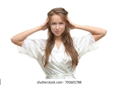 Beautiful young woman in silk bathrobe after shower on white background