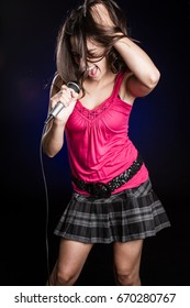 Beautiful young woman singing into microphone