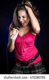 Beautiful young woman singing with microphone