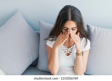 Beautiful young woman with sinus pressure pain. Sinus pain, sinus pressure, sinusitis. Sad woman holding her nose because sinus pain