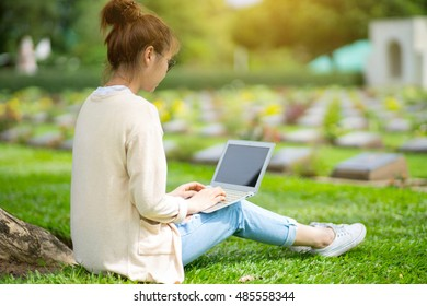 A beautiful young woman sit with the idea for the holiday under a tree in the park.