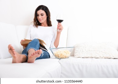 A beautiful young woman siting on a couch reading a book drinking wine and eating popcorn