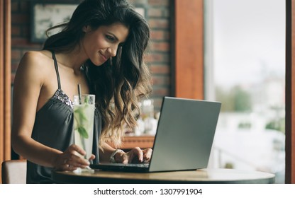 Beautiful young woman sits in cafe. Working on the laptop.