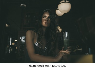 Beautiful young woman sits in dark cafe with sunrises on the face. Texture effect and film grain add. Not camera noise.