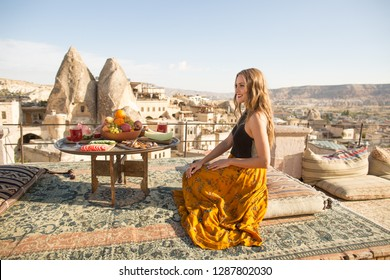 A beautiful young woman sits on one of the Cappadocia roof. Romantic scene.