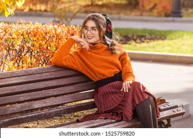 A beautiful, young woman sits on a bench in the fall, in October. The girl is dressed round, with glass glasses. Student teacher is resting, walking in the park.
