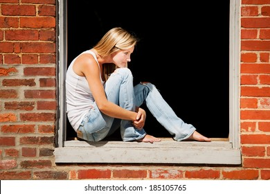 Beautiful young woman sits on window ledge of abandoned brick building.