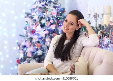 Beautiful young woman sits on sofa near Christmas tree in the house. Merry Christmas and New Year.