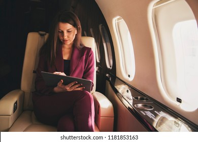 beautiful young woman sits in a plane and works on laptop