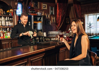 beautiful young woman sitting at the bar talking with the bartender