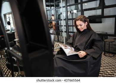 Beautiful young woman sitting in beauty salon and reading fashion magazine