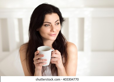 Beautiful young woman sitting in Bed in the Morning and drinking Coffee or Tea and enjoy a relaxing sunny sunday morning