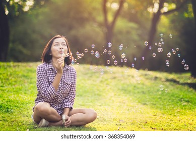 beautiful young woman sitting and  blowing bubble in the park