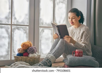 Beautiful young woman sitting by the window and frozen glass. Girl enjoying book.