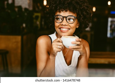 Beautiful young woman sitting at cafe with a cup of coffee and looking away smiling. African female having coffee at coffeeshop.