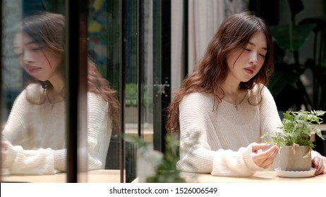 Beautiful young woman sitting in cafe and looking at the green plant on table in sunny day, with her mirror image in glass windows, lonely expression and vintage color.