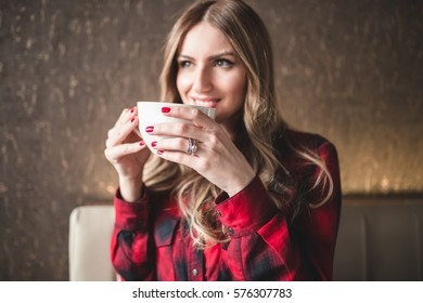 Beautiful young woman sitting in cafe restaurant, relaxing and drinking a coffee. Selective focus on hand.