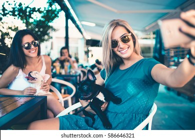 Beautiful young woman sitting in cafe with her adorable French bulldog puppy. Spring or summer city outdoors. People with dogs