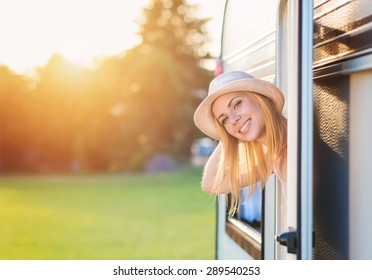 Beautiful young woman sitting in a camper van on a summer day