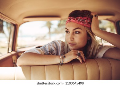 Beautiful young woman sitting in the car and looking away thinking. Thoughtful female wearing bandana in a old car.