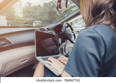 Beautiful young woman sitting in car using laptop,business and working concept with sunshine background.