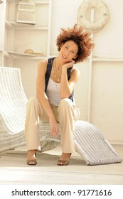 Beautiful young woman sitting in casual home environment on sunny day.