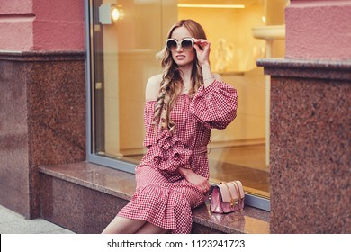 Beautiful young woman sitting in the city. Fashion portrait
