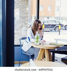 Beautiful Young Woman Sitting in Coffee Shop and Talking on the Phone